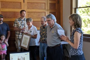 Plumas Unified School District board President Leslie Edlund (right) presents a plaque to the Friends of 50 Committee, who spearheaded the school remodeling. @PlumasUnified